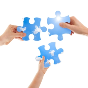 Three hands -male, female and child- holding big puzzle pieces trying to form a picture of the blue sky with sun and clouds. Isolated on white, two clipping paths included one for the puzzle surface and one for the background.
